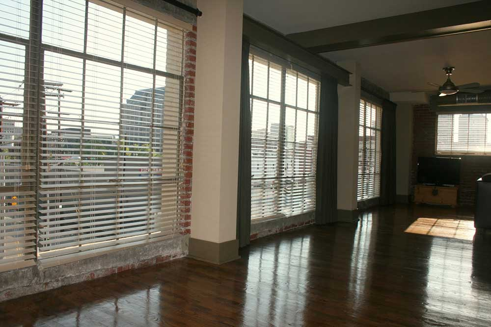 A photo of a living room in Big Lick Junction with hardwood floors, exposed brick, and three floor-to-ceiling windows
