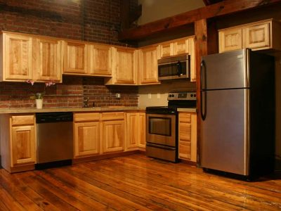 Kitchen in Big Lick Junction apartment unit with hardwood floors, exposed brick walls, stainless steel appliances, and blonde wood cabinetry