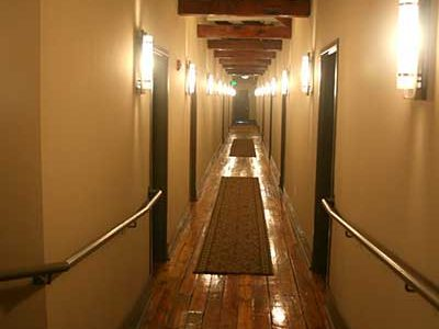 Hallway in common area in Big Lick Junction, with hardwood floors and exposed wooden ceiling beams