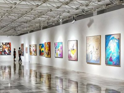 White art gallery with colorful abstract paintings hung on the walls