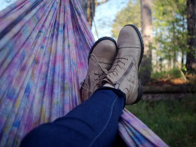 Woman's legs and boots relaxing in a purple tye-dye cloth hammock
