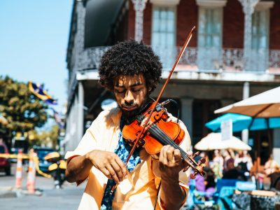 Man plays violin on sidewalk with colorful building and table umbrellas in the background
